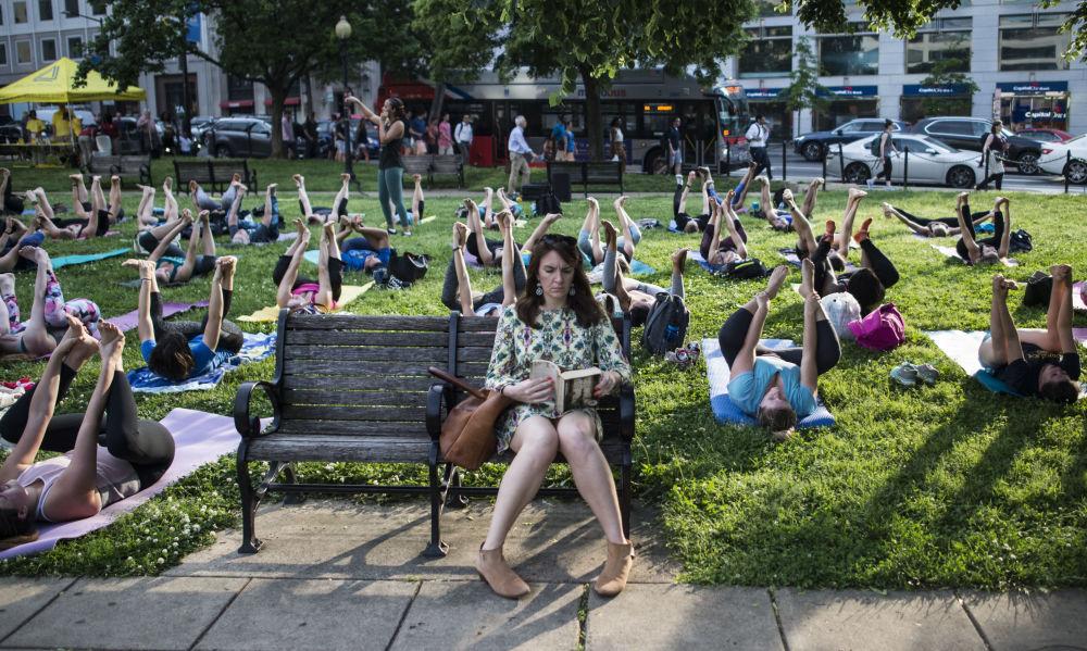 Mulher lê um livro durante uma aula coletiva de yoga ao ar livre em Washington, EUA