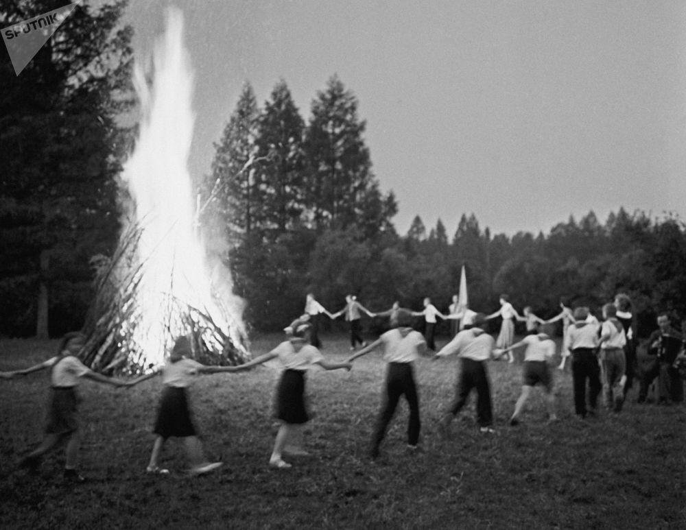 Pioneiros fazem dança popular de roda junto à fogueira em um campo de férias, em 1961