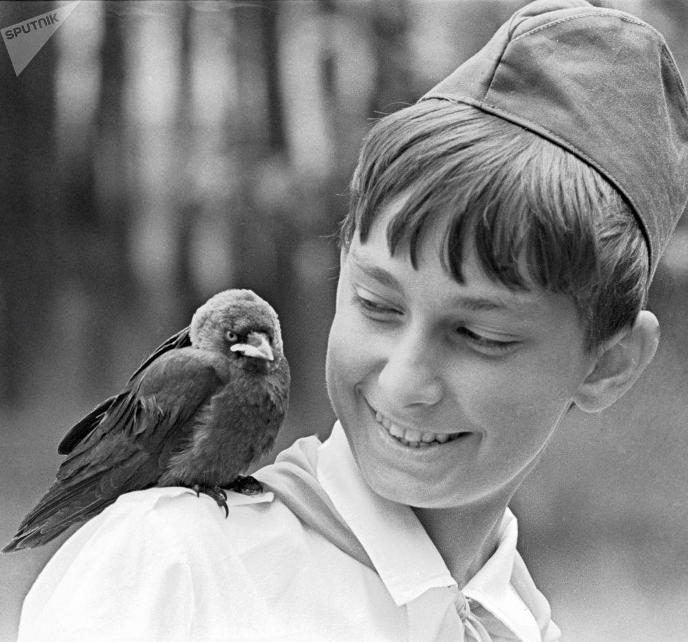 Pequeno corvo é visto sentado no ombro de um pioneiro na ex-república soviética da Bielorrússia, em 1981