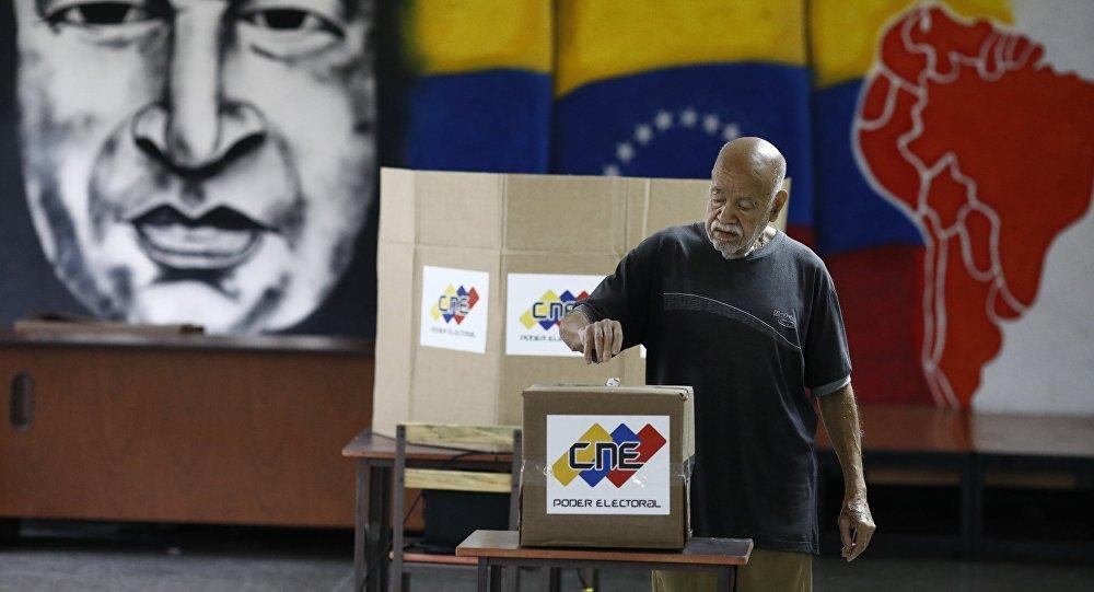 Com uma imagem do falecido presidente venezuelano Hugo Chávez, um cidadão venezuelano deposita seu voto em uma seção de votação durante a eleição presidencial em Caracas, Venezuela, em 20 de maio de 2018.
