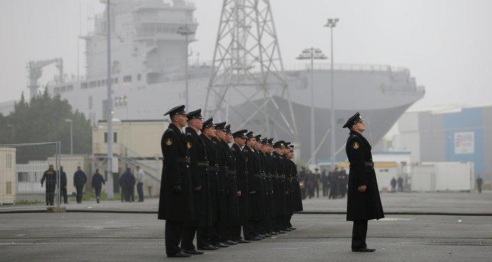 Marinheiros russos em frente a um navio da classe Mistral em Saint-Nazaire, França