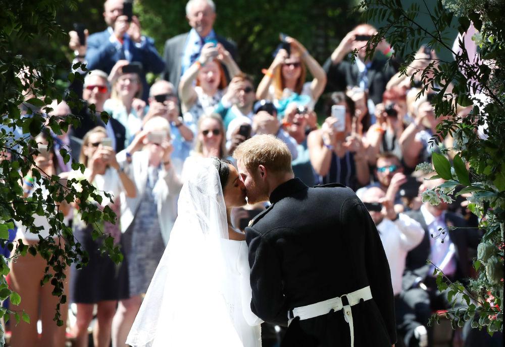 O Príncipe Harry e a sua noiva, Meghan Markle, trocam o primeiro beijo como marido e mulher, após a cerimônia, em frente à Capela de São Jorge, em Windsor