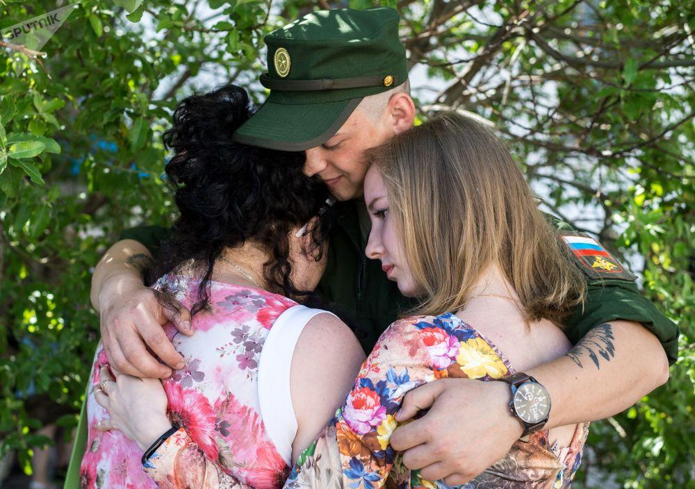 Um jovem conscrito se despede da família e amigos antes de ser enviado para servir na Força Aeroespacial russa