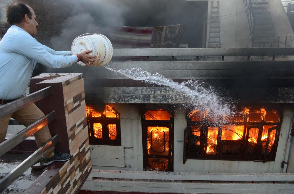 Homem tenta apagar o incêndio em uma loja elétrica na cidade indiana de Amritsar