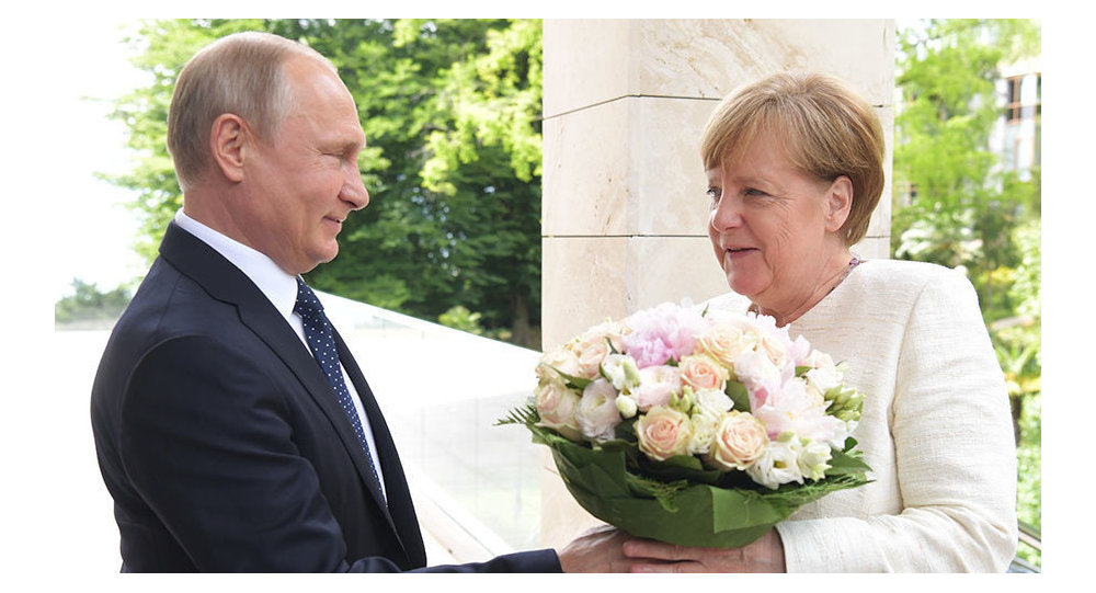 Putin entrega flores à chanceler Angela Merkel.