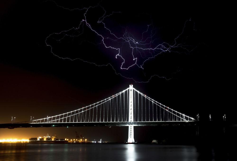 Relâmpagos são vistos no céu sobre a Ponte Bay Bridge, em São Francisco, nos EUA