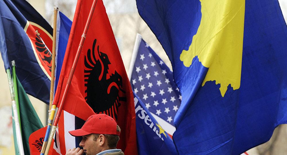 Um homem albanês do Kosovo segura bandeiras em Pristina em 16 de fevereiro de 2011 em preparação para o terceiro aniversário da declaração de independência do Kosovo.