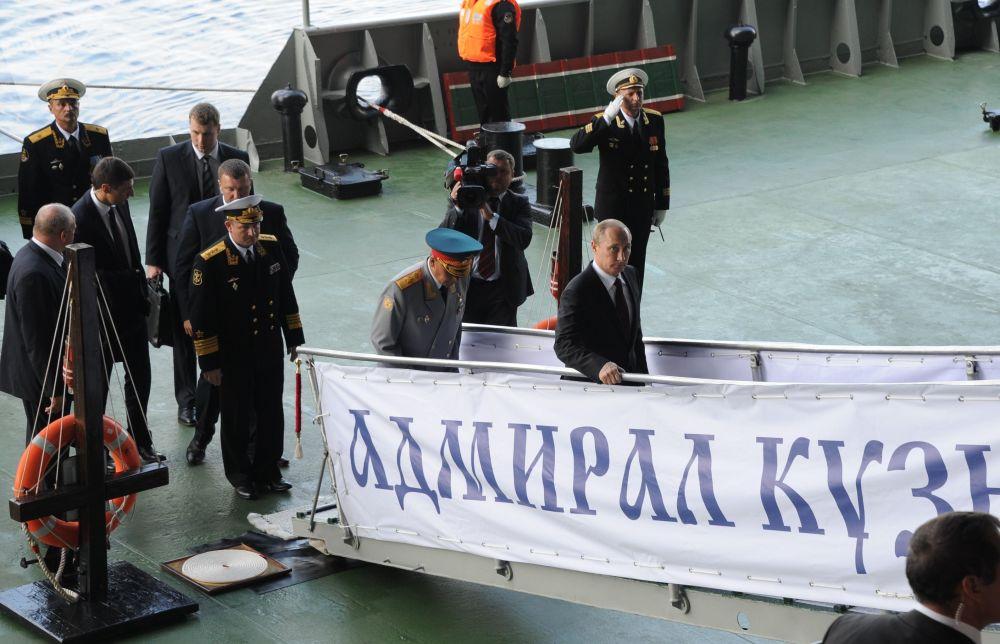 27 de julho de 2014. O presidente russo, Vladimir Putin (à direita), sobe a bordo do cruzador porta-aviões pesado Admiral Kuznetsov durante a celebração do Dia da Marinha da Rússia em Severomorsk