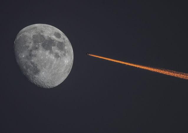 Lua e avião durante o pôr do sol