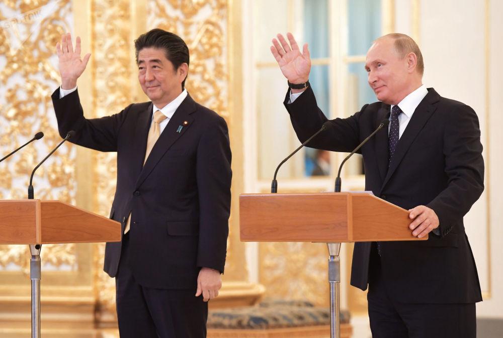 Premiê japonês, Shinzo Abe, e o presidente russo, Vladimir Putin, durante uma ligação de vídeo à tripulação da Estação Espacial Internacional no Kremlin