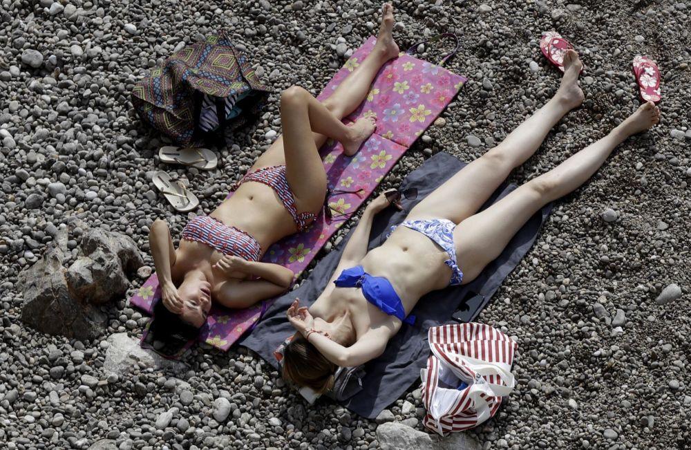 Mulheres tomam banhos de sol durante a corrida de carros Formula Um, em Mônaco
