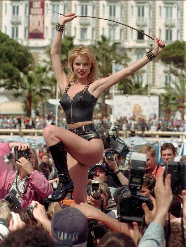Modelo tcheca Eva Herzigova posa em meio à multidão de fotógrafos na Promenade de la Croisette, durante o Festival de Cannes de 1996