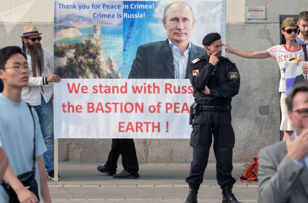 Austríacos segurando um cartaz com a imagem de Vladimir Putin durante seu encontro com o presidente da Áustria Alexander van der Bellen, em Viena.