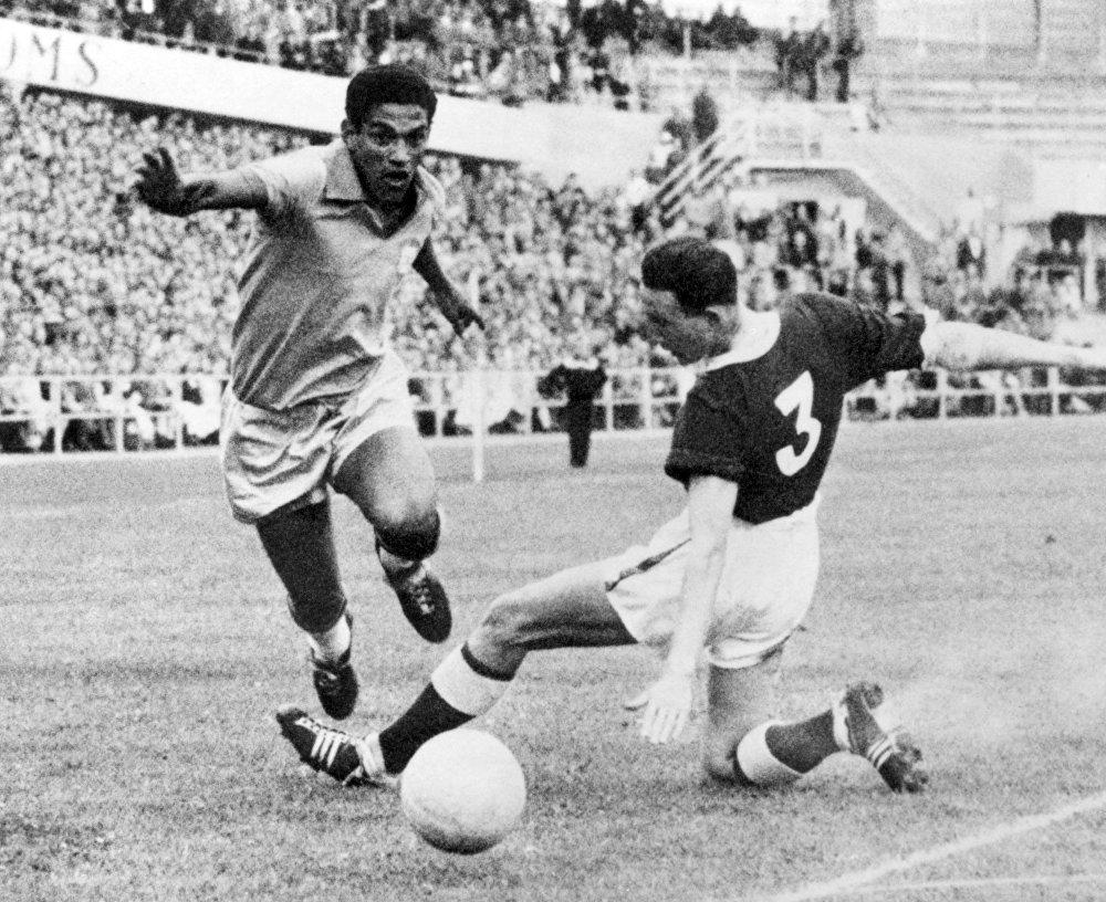 Garrincha dribla o zagueiro do galês Mel Hopkins durante partida de futebol da Copa do Mundo entre Brasil e País de Gales em 19 de junho de 1958, em Gotemburgo. O Brasil avançou para as semifinais com uma vitória de 1 a 0 sobre o gol de Pelé, então com 17 anos.