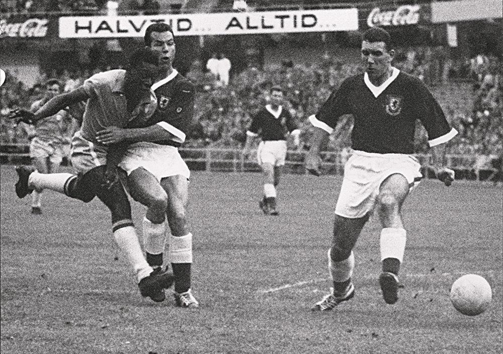 O atacante Pelé, de 17 anos, dribla dois zagueiros do País de Gales durante a partida de futebol das quartas de final da Copa do Mundo entre Brasil e País de Gales em 19 de junho de 1958, em Gotemburgo. Pelé marcou o único gol da partida para ajudar o Brasil a avançar para as semifinais.
