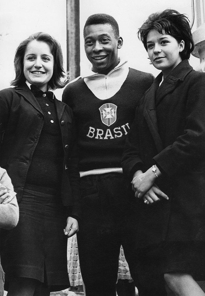 Foto tirada em junho de 1962 em Vina de Mare mostra o atacante brasileiro Pelé com duas torcedoras, poucos dias antes das quartas de final entre Brasil e Inglaterra, em 10 de junho. Pelé não participou da partida e ficou de fora até o final da competição, depois de fraturar um músculo oito dias antes.