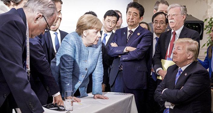 Nesta foto disponibilizada pelo governo federal alemão, a chanceler alemã Angela Merkel fala com os EUA. O presidente Donald Trump é visto sentado à direita durante a Cúpula dos Líderes do G7 em La Malbaie, Quebec, Canadá.