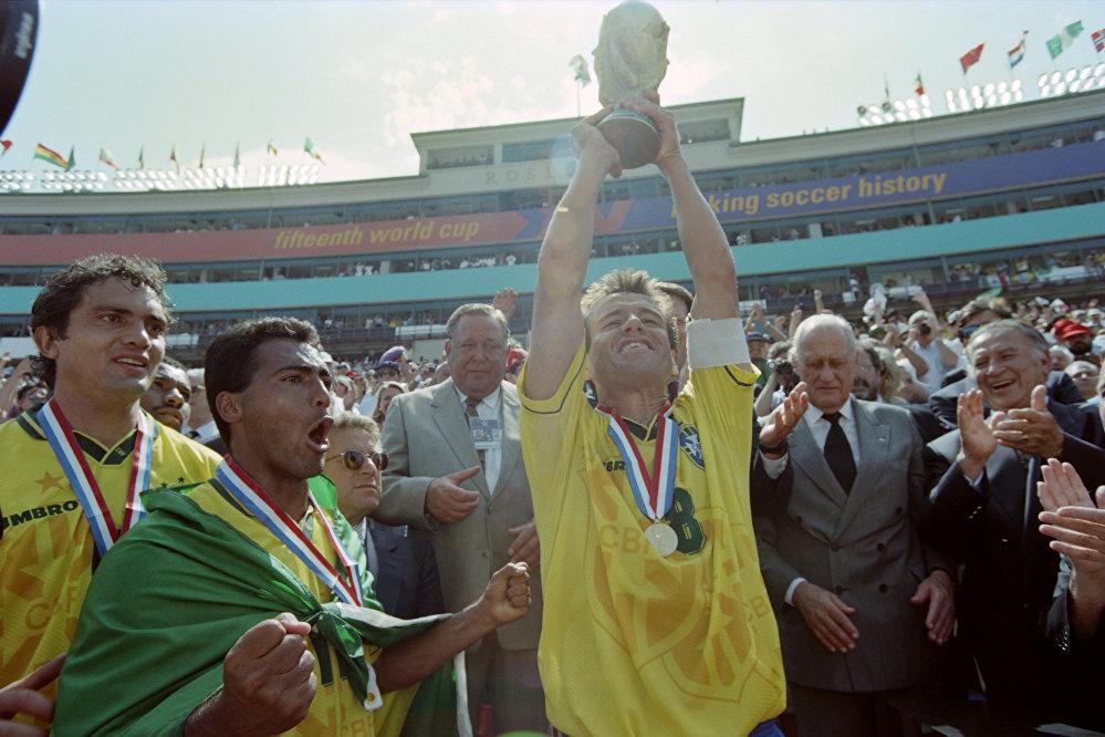 O capitão brasileiro Dunga levanta o troféu da Copa do Mundo da FIFA 1994 ao lado de Romário, após o Brasil derrotar a Itália por 3 a 2 nos pênaltis. O italiano Roberto Baggio perdeu o pênalti e deu ao Brasil o seu quarto título mundial.