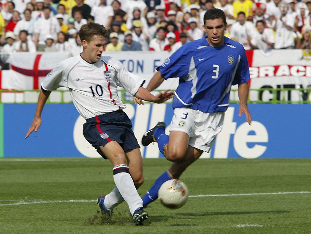O atacante inglês Michael Owen chuta a bola para longe zagueiro brasileiro Lúcio durante a partida entre Inglaterra e Brasil nas quartas de final da Copa do Mundo de 2002.