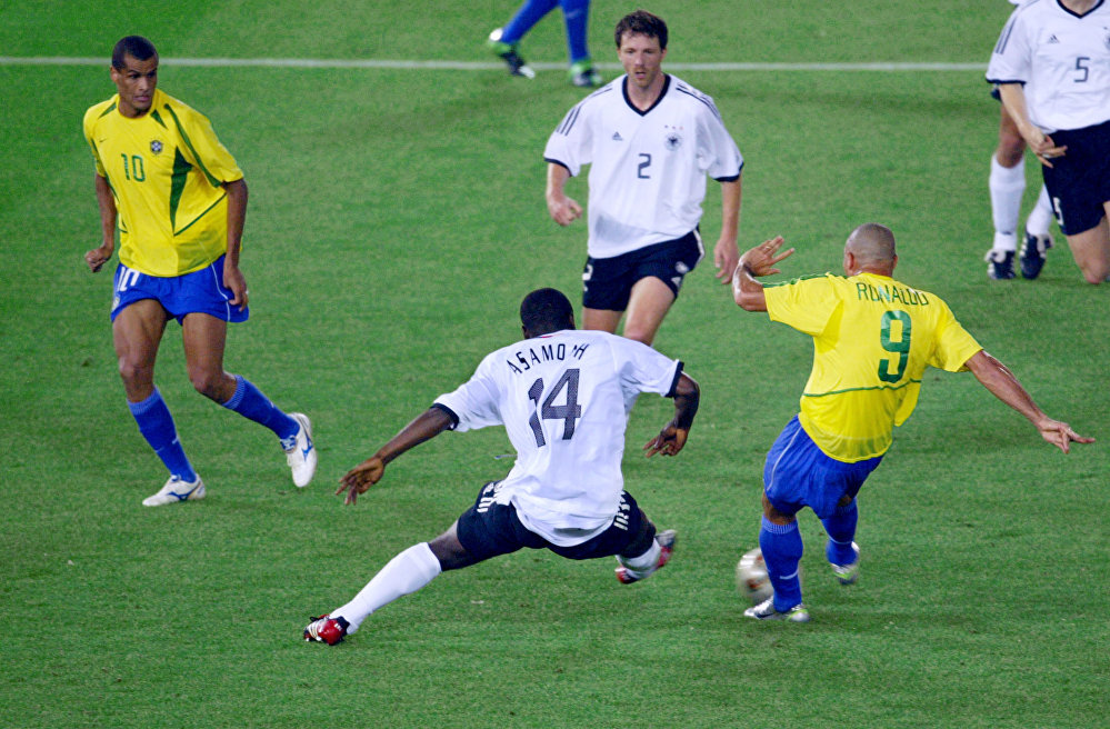 O meia brasileiro Rivaldo e o zagueiro alemão Thomas Linke assistem o atacante da Alemanha Gerald Asamoah tentar impedir o atacante Ronaldo de marcar seu segundo gol durante a final da Copa do Mundo de 2002. O Brasil venceu a final por 2-0.
