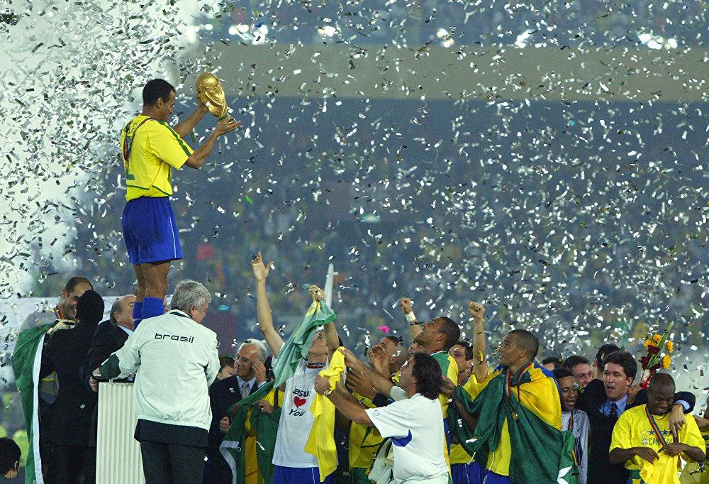 O capitão e zagueiro do Brasil Cafu levanta o troféu da Copa do Mundo sobre seus companheiros comemorando a vitória do Brasil por 2 a 0 sobre a Alemanha na final da Copa do Mundo de 2002 no Estádio Internacional Yokohama, Japão.