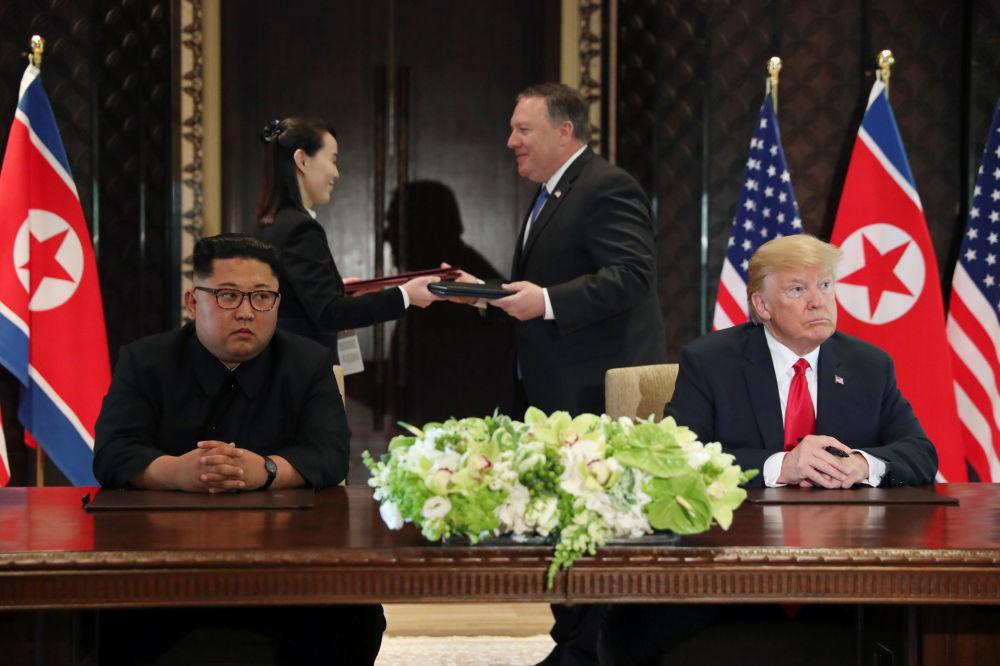 Líder norte-coreano, Kim Jong-un, e o presidente estadunidense, Donald Trump, assinam o documento conjunto após a cúpula histórica em Singapura, em 12 de junho de 2018