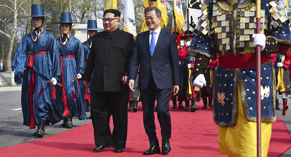 O líder norte-coreano, Kim Jong-un, à esquerda, e  o líder sul-coreano, Moon Jae-in, à direita, caminham juntos na fronteira do vilarejo de Panmunjom, zona desmilitarizada, 27 de abril de 2018