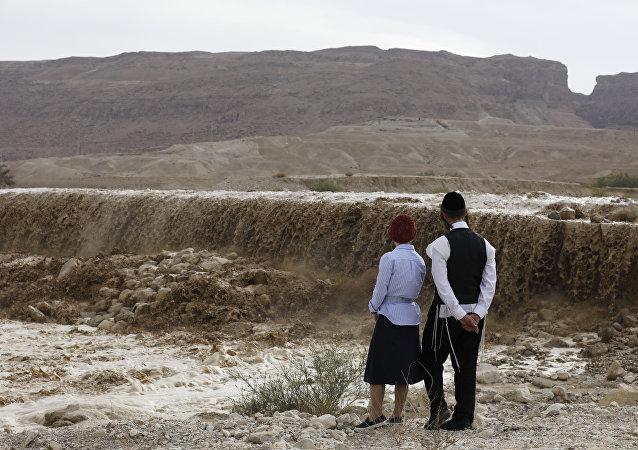 Judeus ultra-ortodoxos observam uma inundação bloqueando a estrada principal ao longo do Mar Morto, no deserto da Judeia (arquivo)