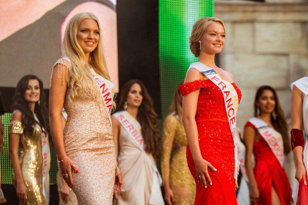 Jovens belas posam no palco em trajes elegantes de cores brilhantes