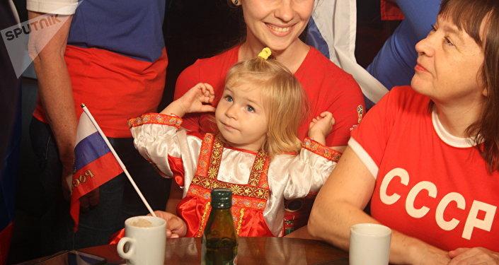 A pequena Arina Timofeeva, 1 ano, vai acompanhar o primeiro jogo de Copa do Mundo na vida. A mãe, Yulia Timofeeva, diz que faz questão de introduzir a menina na cultura russa.