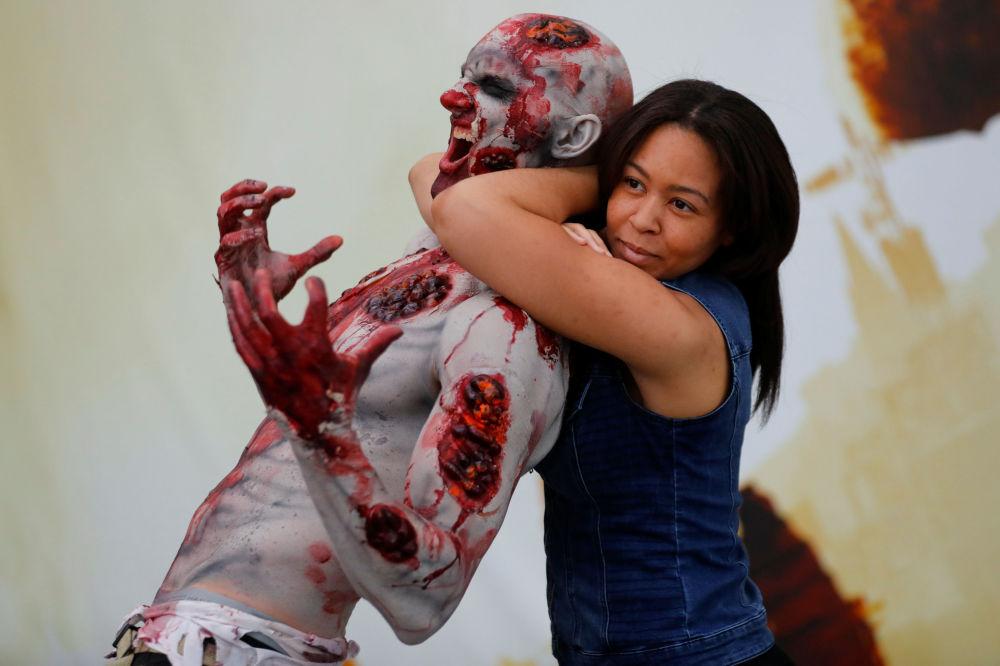 Menina faz uma foto com zombie na feira de videogames e jogos eletrônicos em Los Angeles