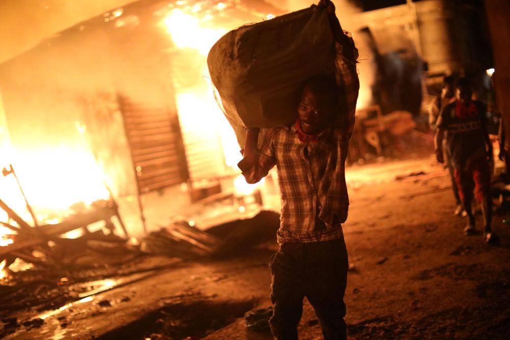 Um vendedor tenta salvar suas mercadorias durante o fogo em um mercado de Porto Príncipe, Haiti