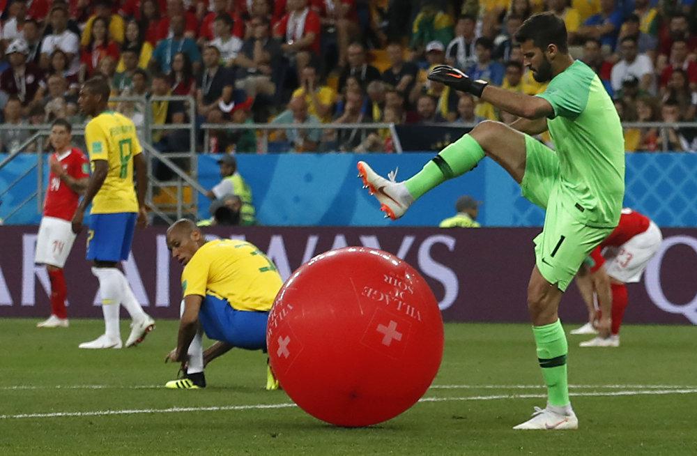 Goleiro Alison tenta furar balão suíço em campo durante partida entre Brasil e Suíça.