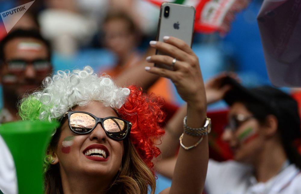 Torcedora iraniana tirando foto ao assistir ao jogo entre Irã e Marrocos.