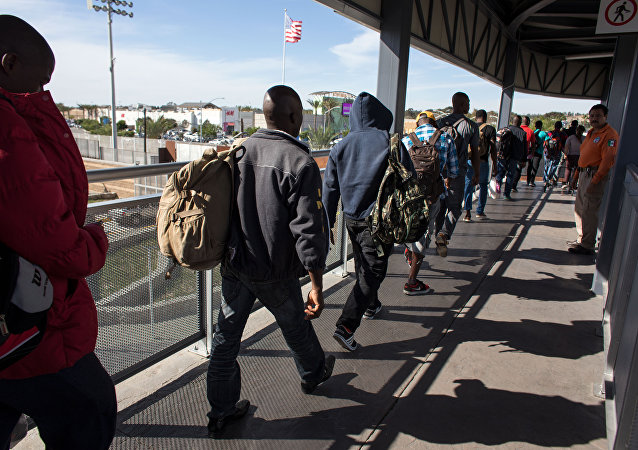 Migrantes haitianos que procuram asilo nos Estados Unidos fazem fila frente a um prédio na fronteiriça cidade mexicana de Tijuana.