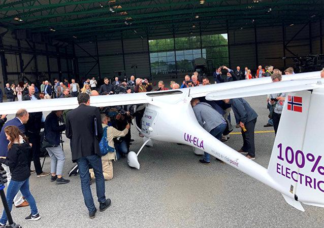 Pessoas cercando o avião elétrico de dois assentos fabricado na Eslovênia