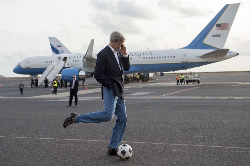 Secretário de Estado John Kerry chutando bola enquanto fala pelo celular durante paragem para reabastecimento do avião em Cabo Verde, 2014