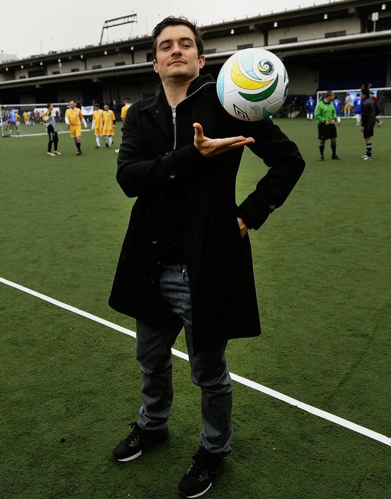 Ator britânico Orlando Bloom posando com uma bola de futebol, EUA, 2011