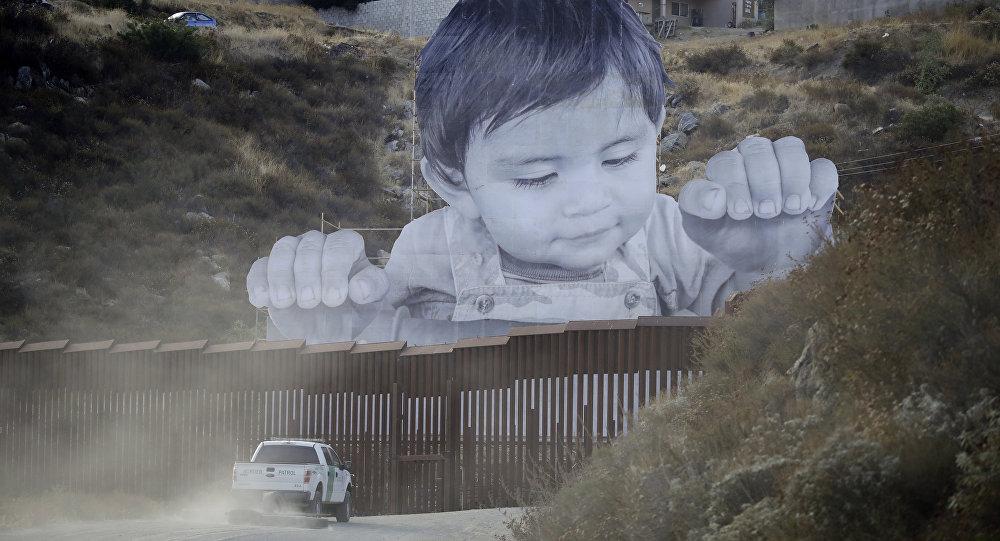Um veículo da Patrulha da Fronteira dirige em frente a um mural em Tecate, no México, logo depois de uma estrutura fronteiriça.