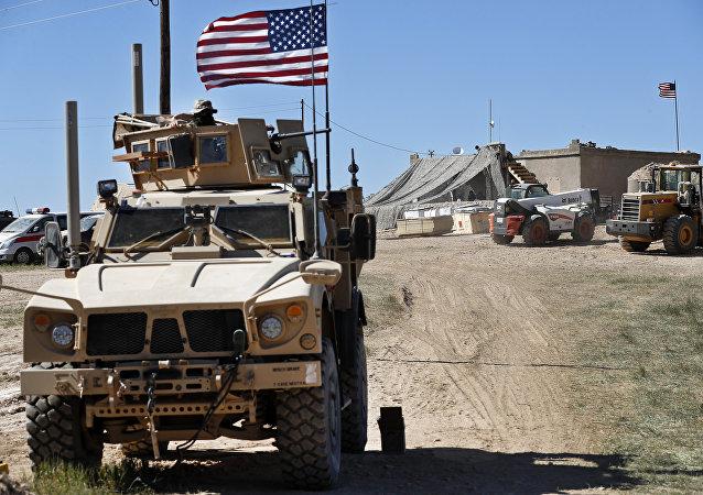 Soldado norte-americano, à esquerda, sentado em veículo blindado perto da tensa linha de frente entre o Conselho Militar de Manbij, apoiado pelos EUA, e os combatentes apoiados pelos turcos, em Manbij, norte da Síria, 4 de abril de 2018