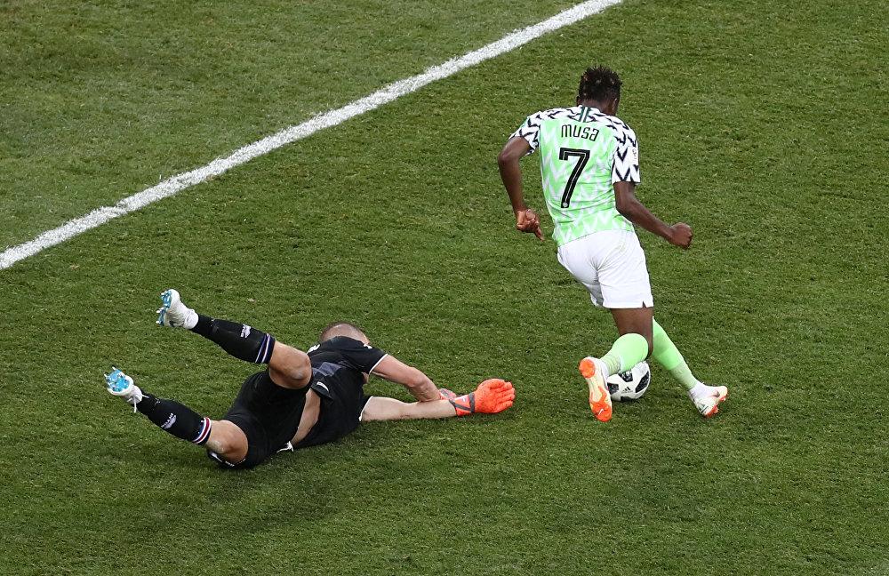 Ahmed Musa, da Nigéria, deixa no chão o goleiro Hannes Halldorsson, que já parou Lionel Messi nesta Copa do Mundo, para marcar um dos gols da vitória nigeriana por 2x0.