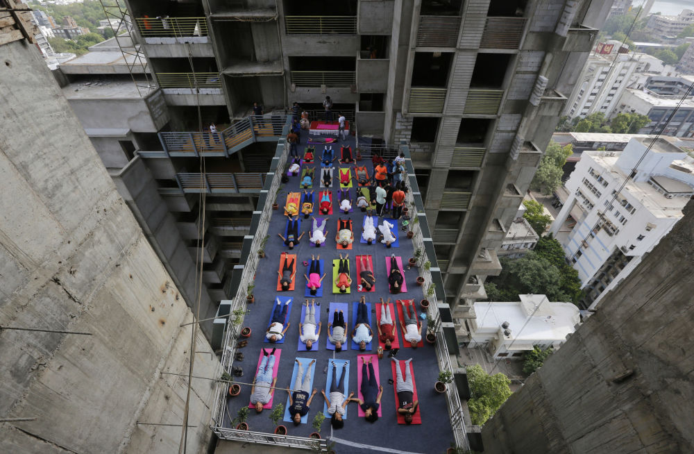 Indianos praticando ioga entre duas torres de um edifício residencial em construção por ocasião do Dia Internacional do Ioga, em Ahmadabad, Índia.