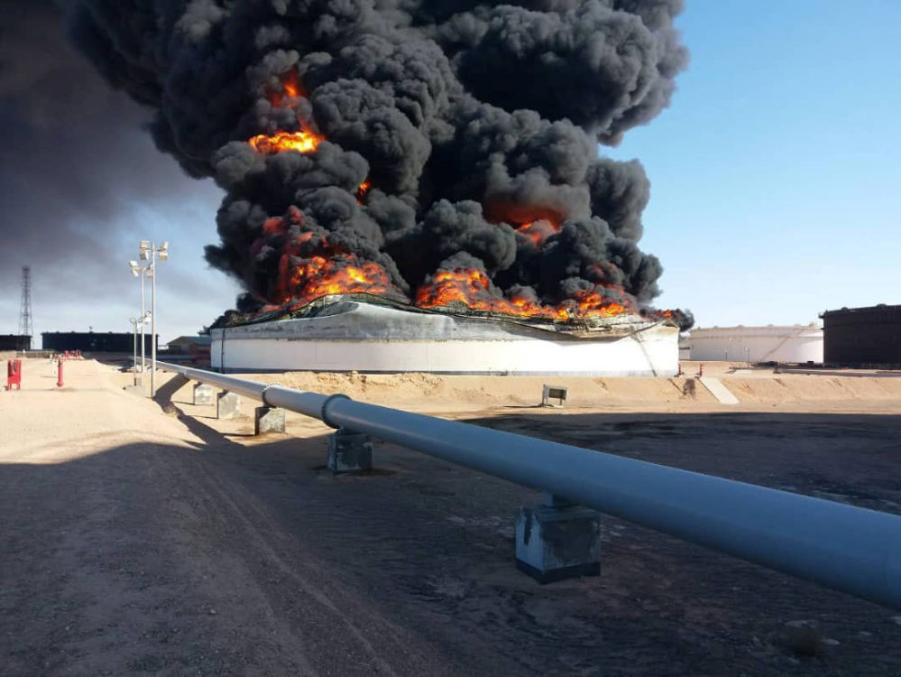 Fumaça e chamas subindo sobre um tanque de armazenamento de petróleo incendiado durante um combate entre grupos rivais em Ras Lanuf, Líbia.