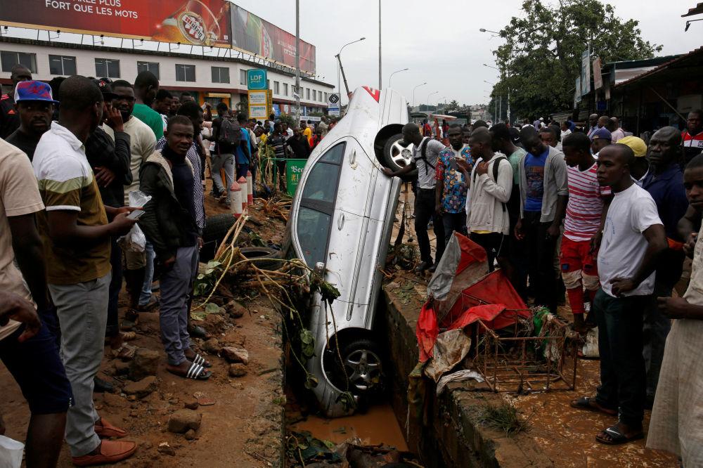 Pessoas observando um carro que caiu em um esgoto após uma inundação em Abidjan, Costa do Marfim.