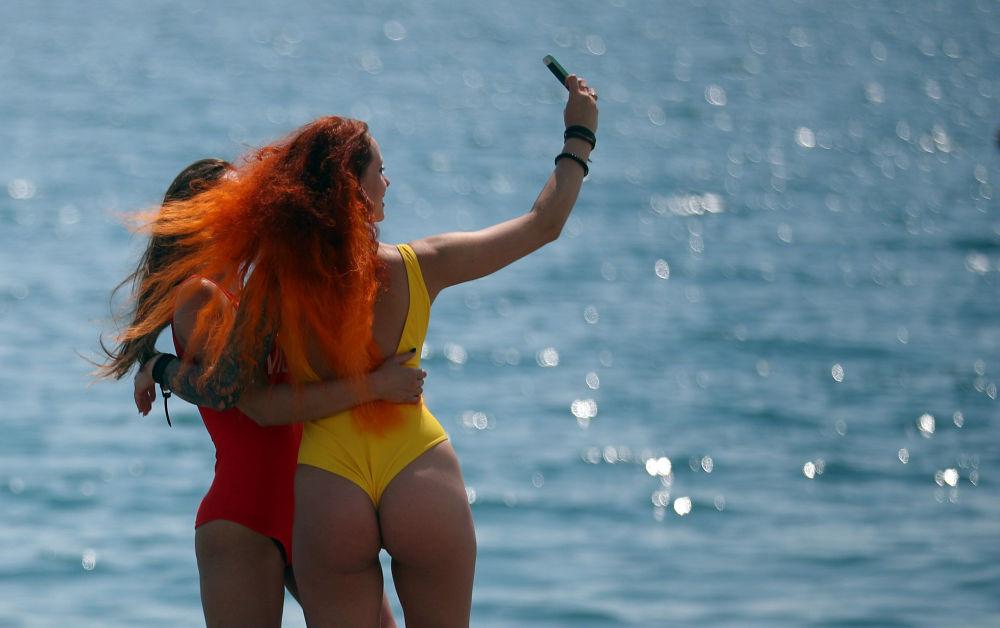 Jovens tirando selfie em uma praia em Sochi, Rússia.