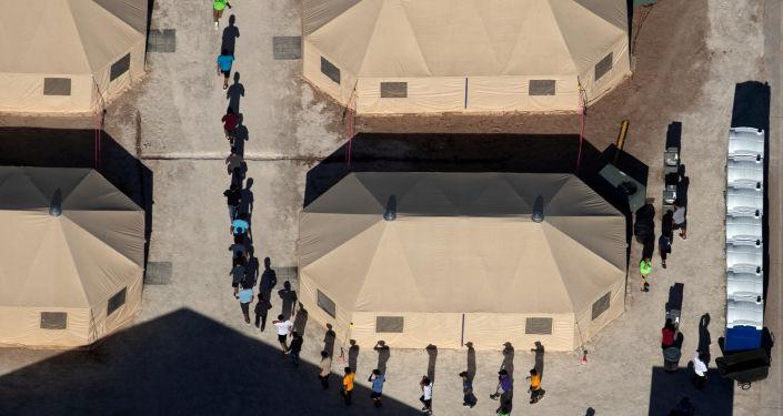Crianças imigrantes conduzidas por funcionários em fila indiana em um cento de detenção perto da fronteira mexicana em Tornillo, Texas, EUA.