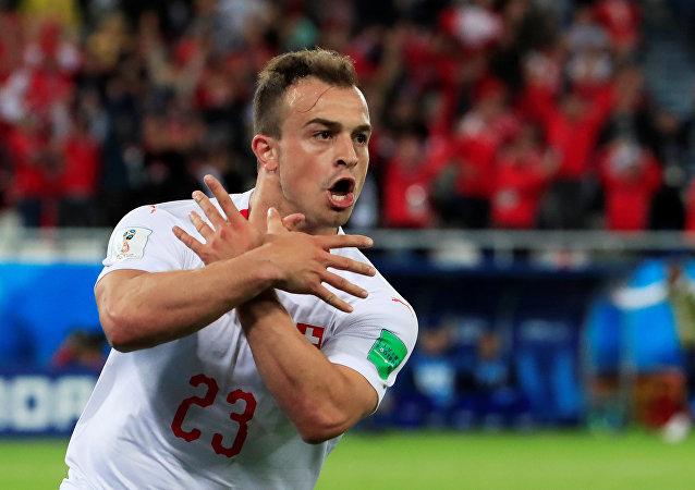 O suíço Shaqiri comemora seu gol na vitória da seleção da Suíça contra a Sérvia durante a fase de grupos da Copa do mundo de 2018. O símbolo que ele faz seria uma representação da águia da bandeira albanesa, e foi considerado uma provocação contra a Sérvia. A FIFA abriu investigação sobre o caso.
