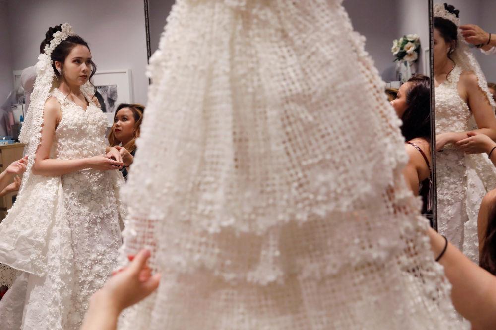 Modelo se prepara antes de sair ao palco durante o 14º Concurso Anual de Vestidos de Noiva de Papel Higiênico em Nova York