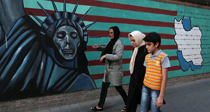 Família iraniana caminha em frente a grafite anti-Estados Unidos em Teerã.