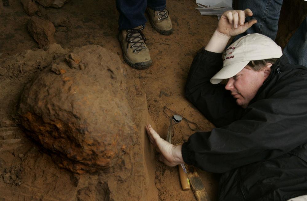 Pesquisador do Museu de Ciência Natural de Houston examina solo sob um meteoro